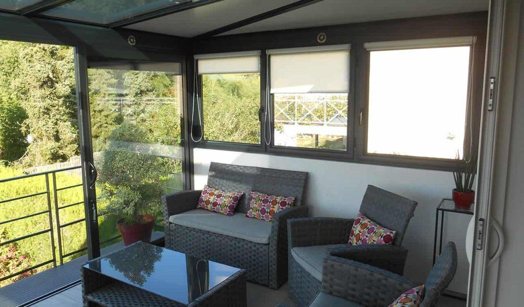Véranda aluminium avec baies vitrées et fenêtres, équipées de stores. Réalisation Design Vérandas à Saint-Hilaire de Mortagne 85