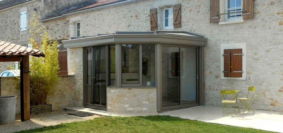 Petite véranda classique pour sas d'entrée, aluminium gris clair - Réalisation Design vérandas à Thiré 85