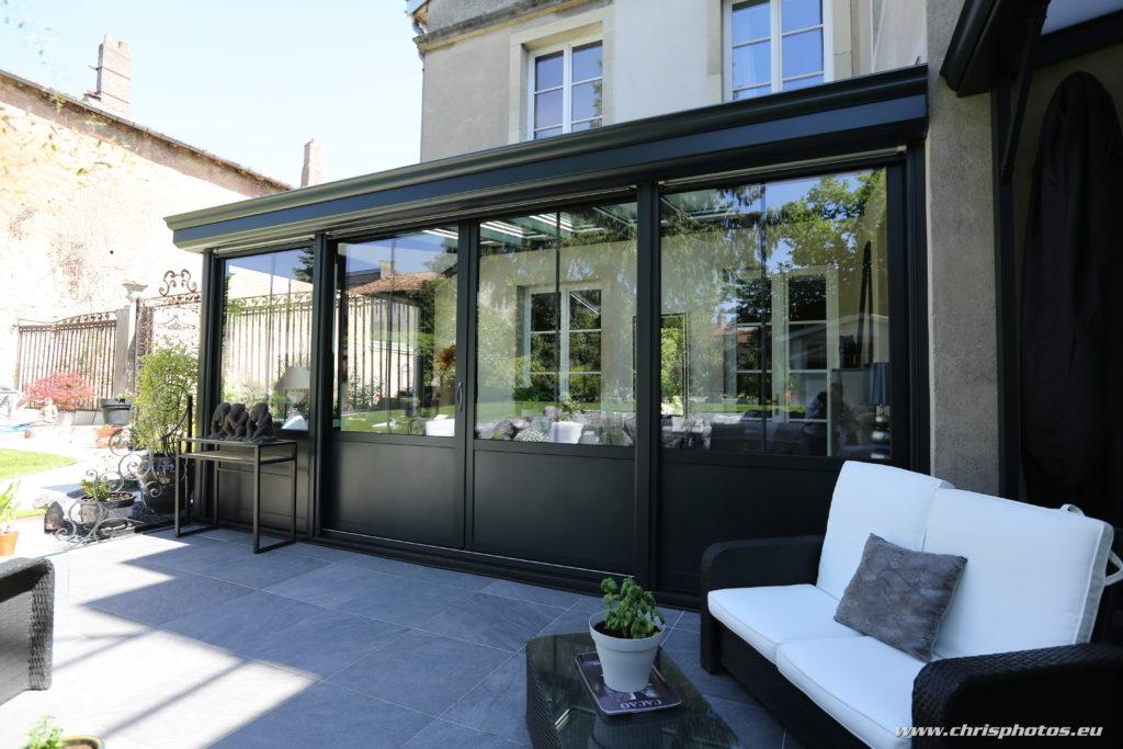 Véranda Rénoval style ancien en aluminium noir, pour maison de caractère.
